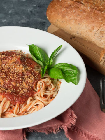 Bowl of pasta with oil-free marinara and loaf of multi-grain bread