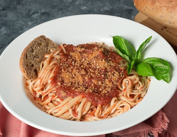 White bowl of pasta with Oil Free Marinara, a slice of whole grain bread, a sprig of basil