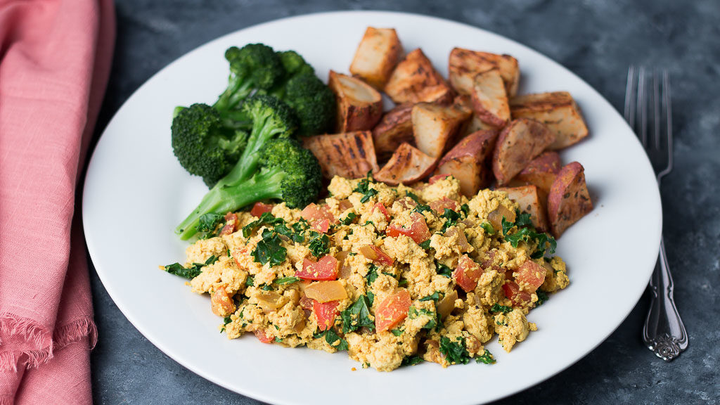 Plate of tofu scramble with roasted potates and broccoli