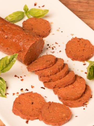 Vegan Pepperoni sliced on a platter with basil garnish