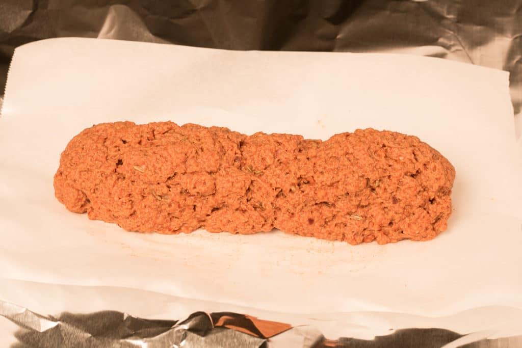 Pepperoni seitan dough formed into a log before baking