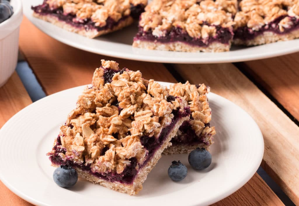 Plate with two Blueberry Oat Bars and some fresh blueberries. More bars in the background.