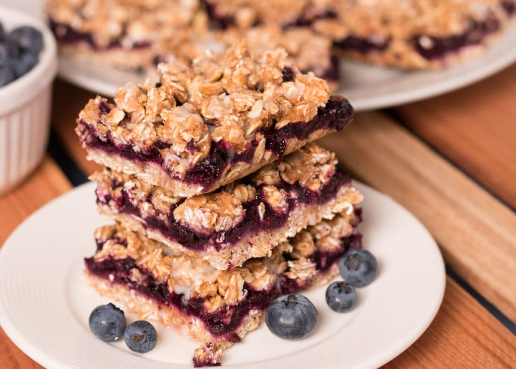 Three Blueberry Oat Bars with lemon glaze stacked on a small plate. More bars in the background.