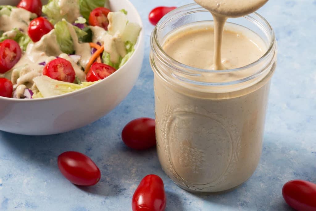 Jar of oil-free Savory Garlic Dressing and bowl of salad