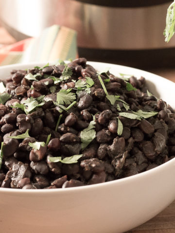 Bowl of Savory Black Beans with Instant Pot in the background