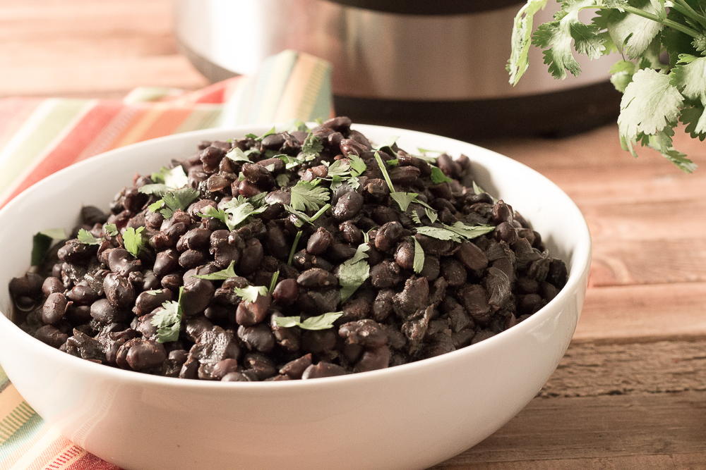 Bowl of Savory Black Beans with Instant Pot and cilantro in the background