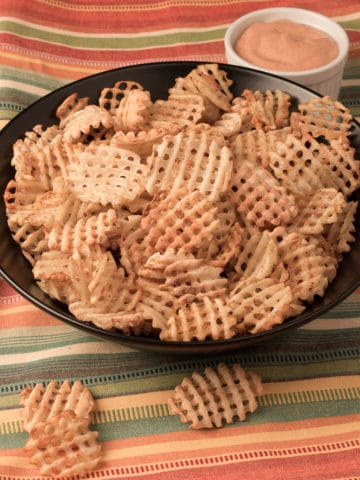 Bowl of Seasoned Waffle Fries with dipping sauce