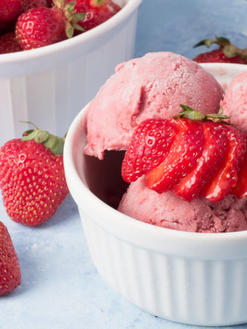 Bowl of vegan strawberry ice cream and bowl of strawberries in background