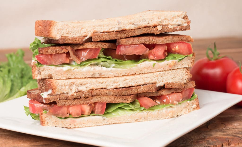 Plate with Tofu BLT, with lettuce and tomato in background