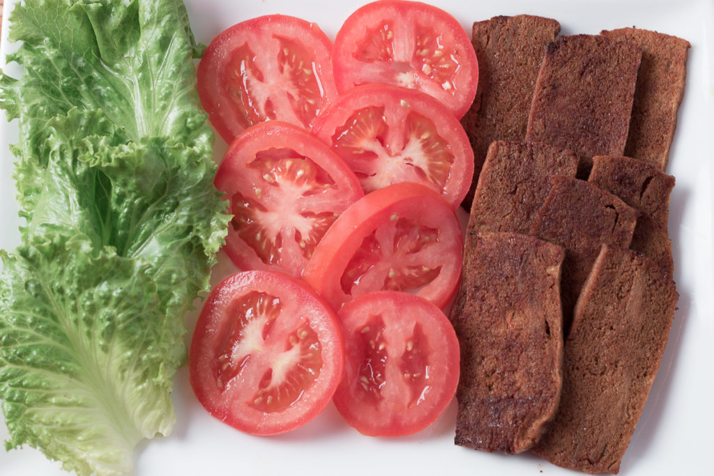 Plate of tofu bacon, lettuce leafs and tomato slices ready for TLT sandwiches