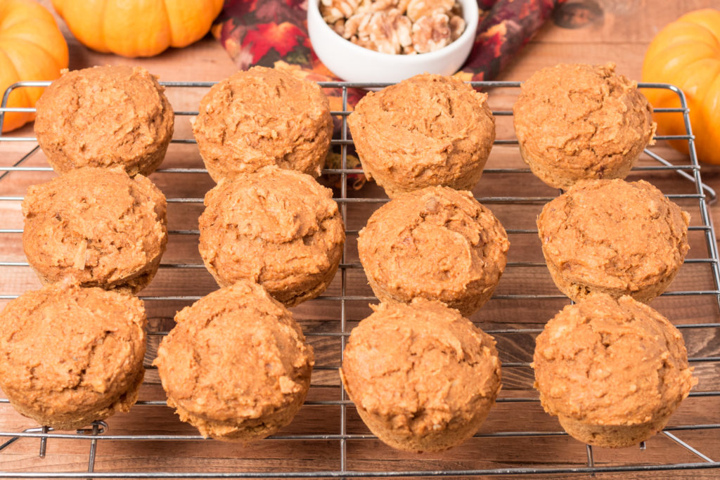 Vegan Pumpkin Muffins on a cooling rack with mini pumpkins, bowl of walnuts, and fall napkin in background