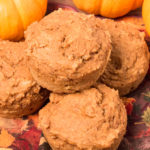 Four stacked Vegan Pumpkin Muffins on a fall napkin with mini pumpkins in background