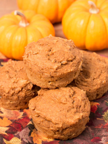 Four Vegan Pumpkin Muffins stacked on a fall napkin with three mini pumpkins in background
