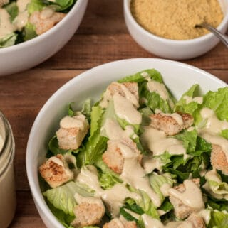 Photo of two bowls of Vegan Caesar Salad on wooden board, with jar of Caesar dressing and bowl of nutritional yeast in background