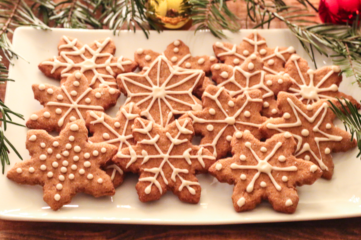 White plate of Oil-Free Vegan Gingerbread cookies, cut into snowflake shapes. Fir branches and red and gold Christmas ornaments surround the plate.