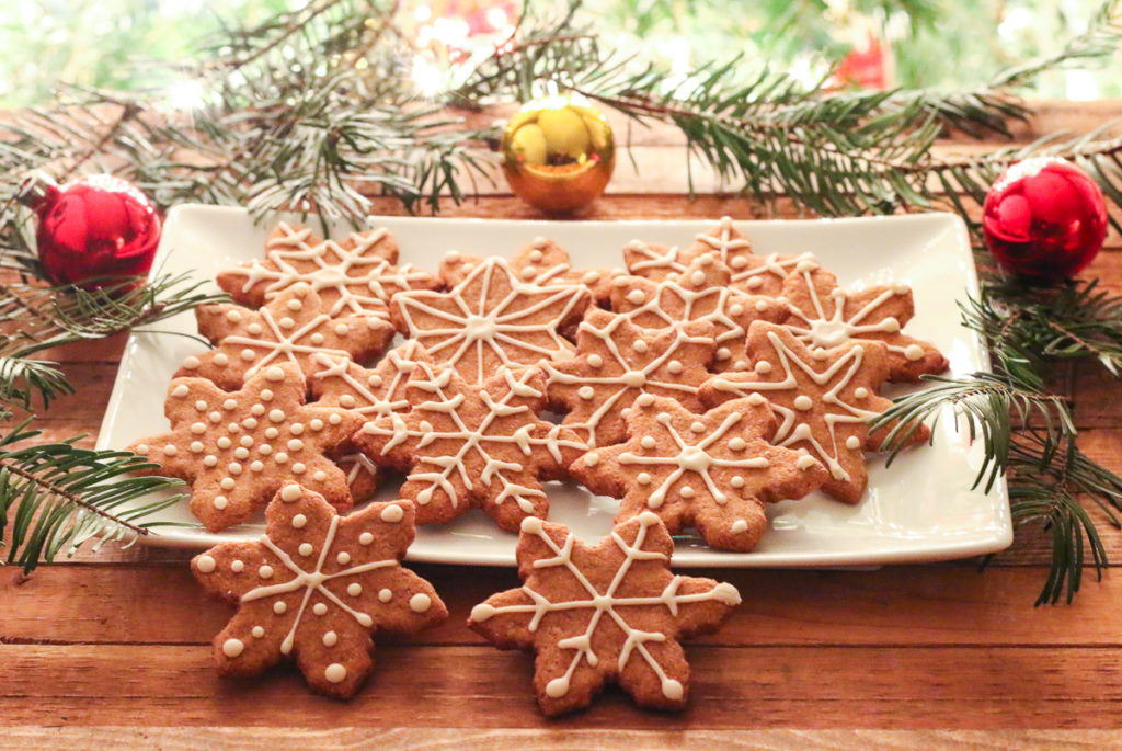 White plate of Oil-Free Vegan Gingerbread cookies, cut into snowflake shapes. Fir branches and red and gold Christmas ornaments surround the plate. Lit Christmas tree branches in background.
