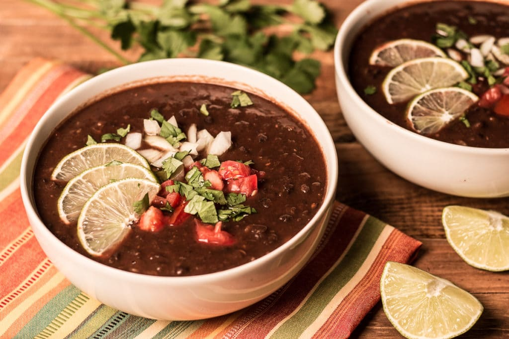 Two bowls of vegan black bean soup on a striped napkin, with cilantro and lemon wedges in backgroung