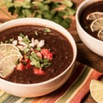 Two bowls of black bean soup on a striped napkin, with cilantro and lemon wedges beside them