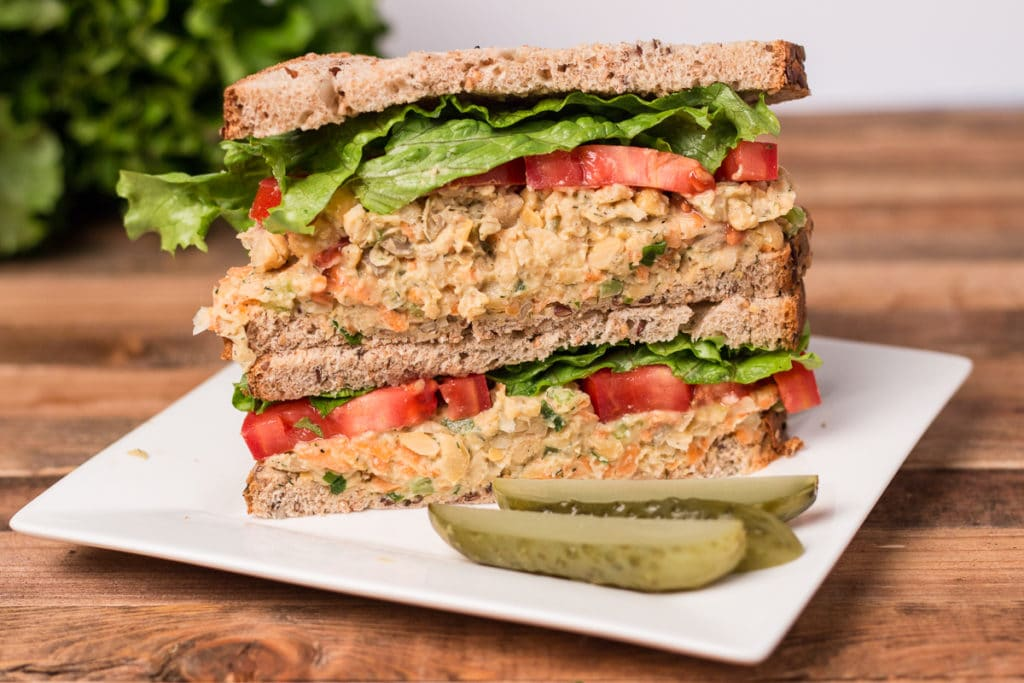 Chickpea salad sandwich on a plate with pickle spears