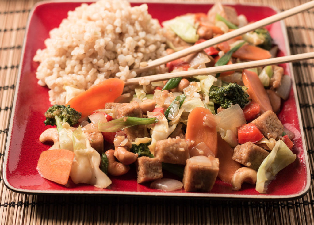 Closeup photo of stir fry and rice on a square red plate with chopstics