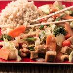 Closeup shot of stir fry on red plate with chopsticks