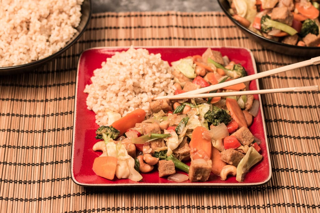 Square red plate with Cashew Veggie Stir Fry, sitting on a woven mat, with rice and additional stir fry in background