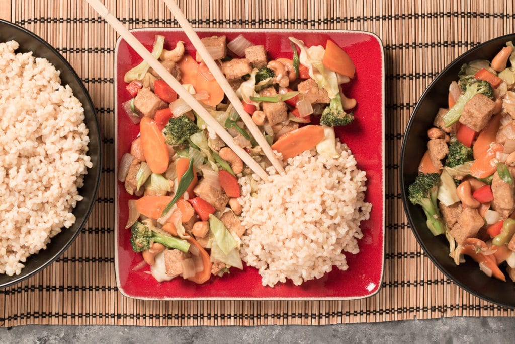 Square red plate with Cashew Veggie Stir Fry and rice, with chopsticks. Bowl of rice to the left of plate, and bowl of stir fry to the right of plate.