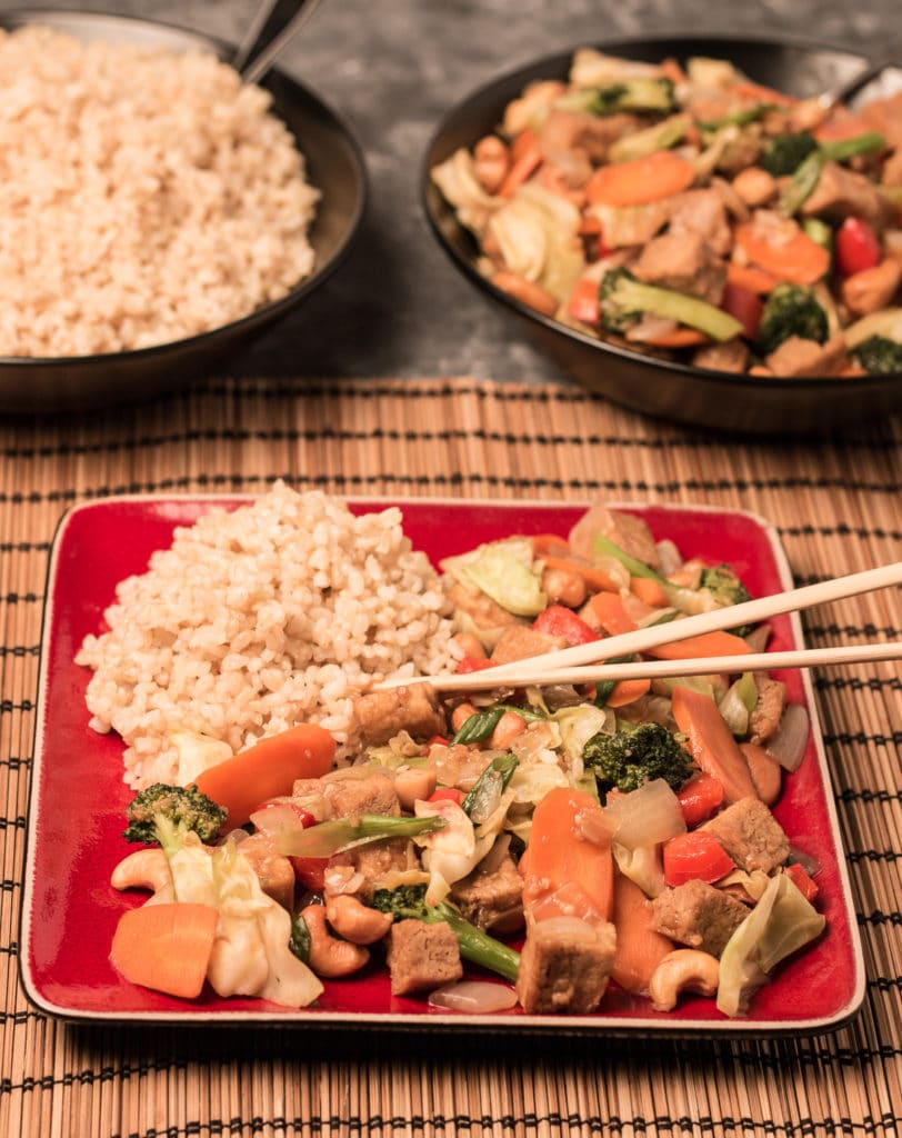 Vertical photo of stir fry on square red plate, sitting on woven mat, with bowl of rice and bowl of stir fry in background