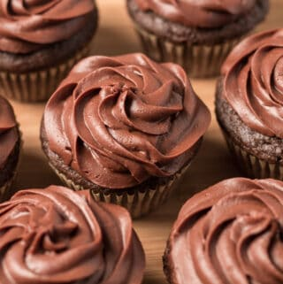 Picture of seven chocolate cupcakes on wooden tray