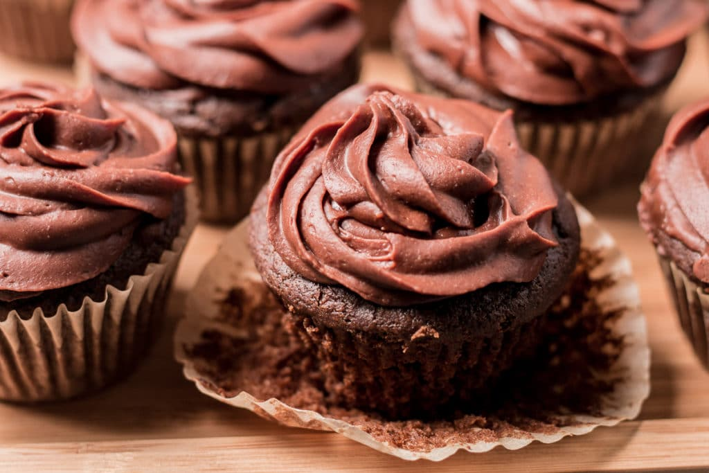 Chocolate cupcakes, one with paper liner peeled back