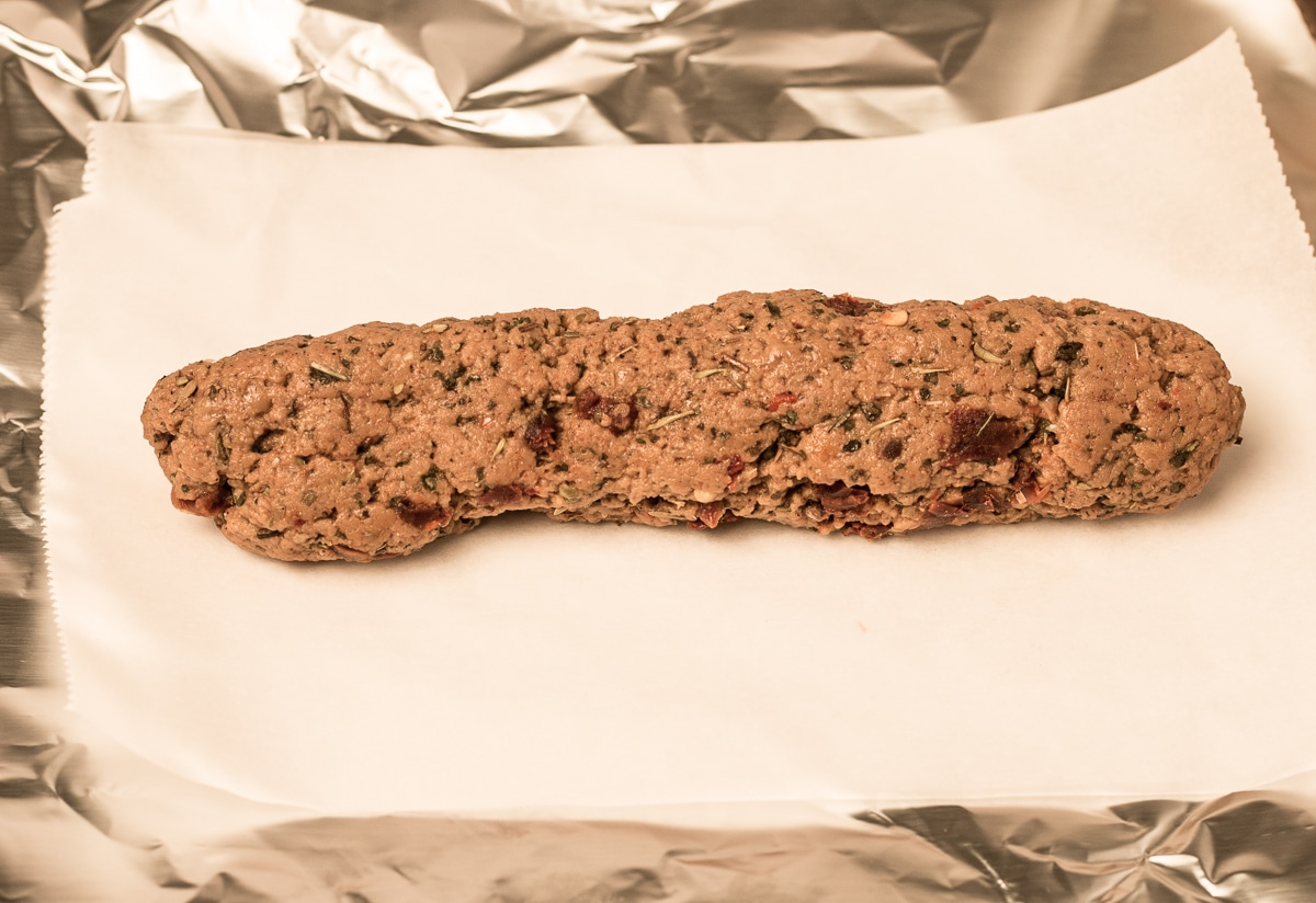 Seitan dough formed into a sausage shape, on parchment and foil, ready to be wrapped and cooked