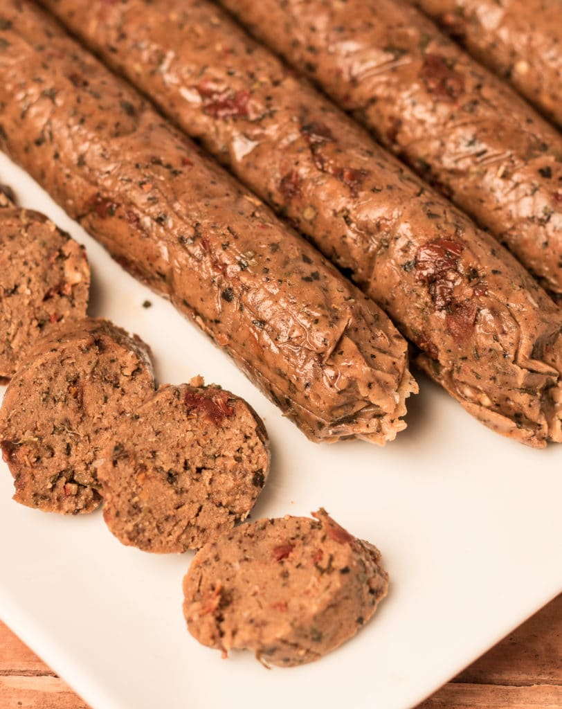 White platter with whole and sliced seitan Italian sausages
