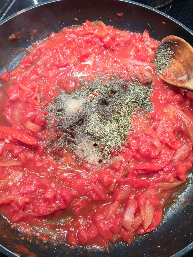 Tomatoes and herbs added to peppers & onions in nonstick pan