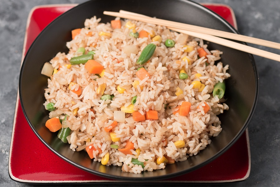 Bowl of Easy Vegan Fried Rice in black bowl with chopsticks, sitting on square red plate