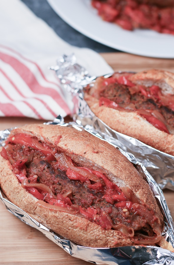 Two Italian sausage sandwiches wrapped in foil, sitting on wooden board with napkin and plate of sausage & peppers in background