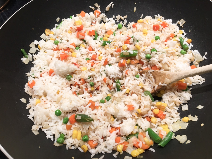 Rice added to vegetables in wok