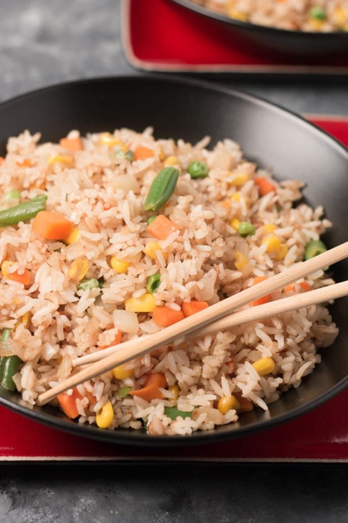 Vertical image of black bowl of fried rice with chopsticks, sitting on square red plate, with another bowl of fried rice in background