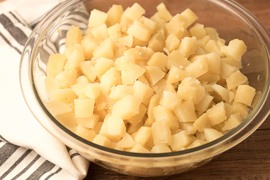 Glass bowl of diced potatoes and striped napkin on wooden surface