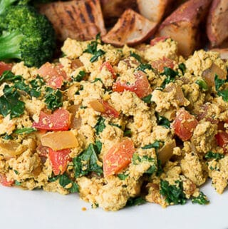 Closeup view of tofu scramble with kale and diced tomatoes; broccoli and roasted potatoes in background
