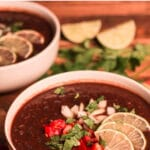 Two bowls of soup with cilantro and lime in background, Pinterest title above photo