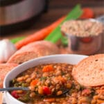 Bowl of lentil soup with spoon and slice of bread in the bowl; more bread, carrots, celery, garlic, and lentils in the background, Pinterest title above image