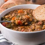 Bowl of lentil soup with spoon of soup and slice of bread in the bowl, more bread in background