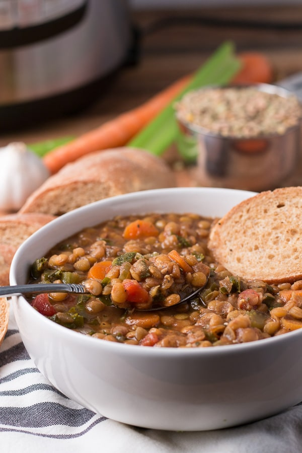 Bowl of lentil soup with spoon and slice of bread in the bowl; more bread, soup ingredients, and Instant Pot in the background