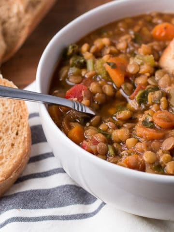 Bowl of lentil soup with spoon of soup and slice of bread in the bowl, more bread beside the bowl