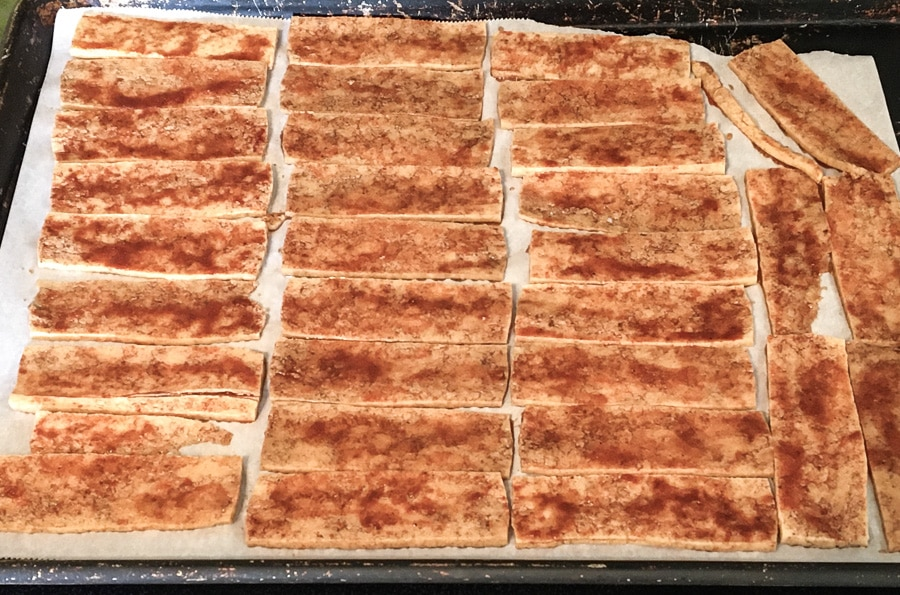 Marinated tofu slices on a parchment covered baking sheet