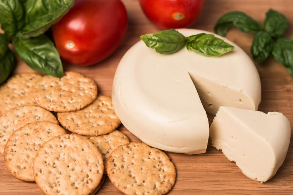 Wheel of vegan cheese with wedge cut out of it, tomatoes, basil, and crackers, background