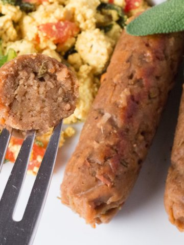 For with a piece of breakfast sausage in front of a plate with tofu scramble and breakfast sausages