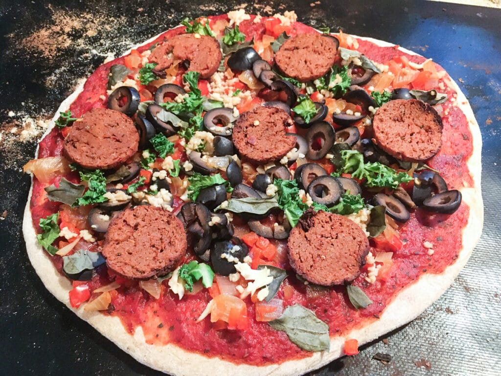 Pizza with vegan pepperoni, ollives, and veggies