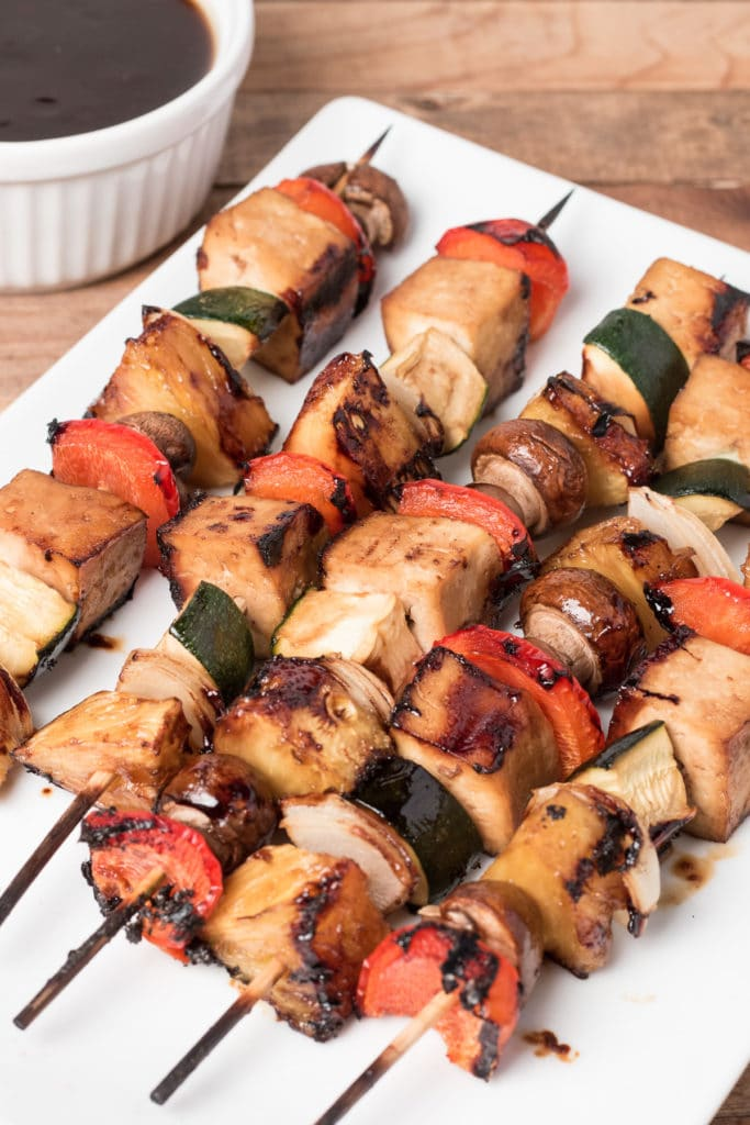 Veggie kabobs on a white platter with bowl of sauce next to them
