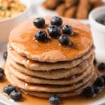 Stack of pancakes topped with blueberries and maple syrup; breakfast sausage, tofu scramble, and blueberries in background